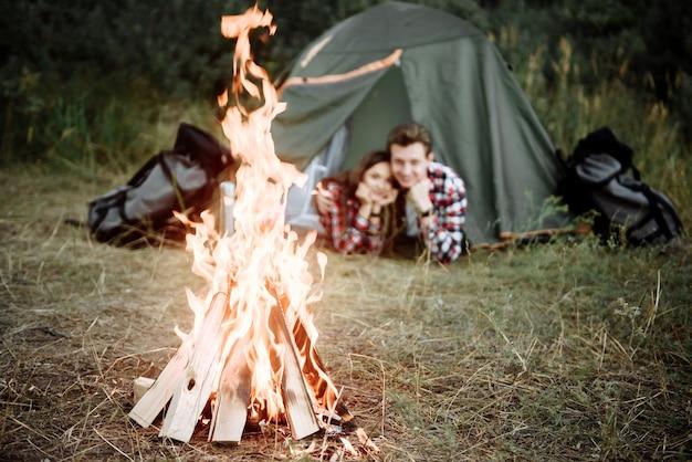 Jovem casal de turistas, homem e mulher, descansando em um acampamento, perto de uma fogueira e uma barraca verde na natureza
