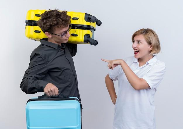 Jovem casal de turistas, mulher feliz apontando com o dedo indicador para o namorado descontente com malas em pé sobre uma parede branca