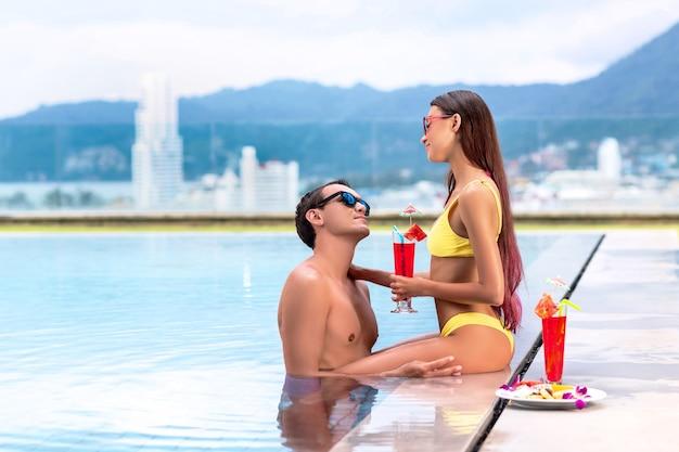 Jovem casal de turistas na piscina infinita bebendo coquetéis em resort na praia