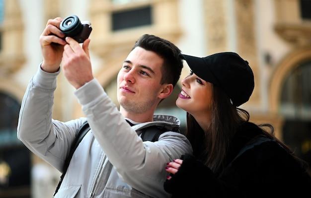 Jovem casal de turistas tirando fotos na cidade