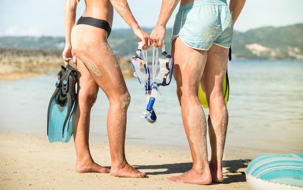 Jovem casal de veranistas apaixonado se divertindo na praia de phuket na tailândia com máscara de snorkel e barbatanas