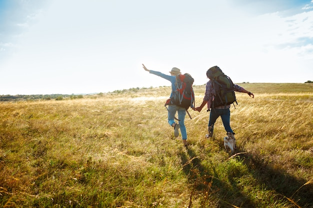 Jovem casal de viajantes andando no campo com cão pug