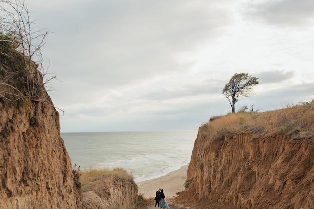 Jovem casal de viajantes beijando perto de uma vista deslumbrante perto das colinas de areia e água azul. copie o espaço.