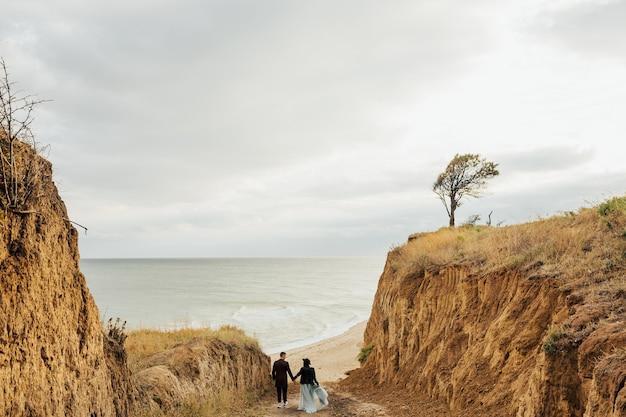 Jovem casal de viajantes na estrada para o mar com vistas deslumbrantes sobre as colinas de areia e águas azuis.