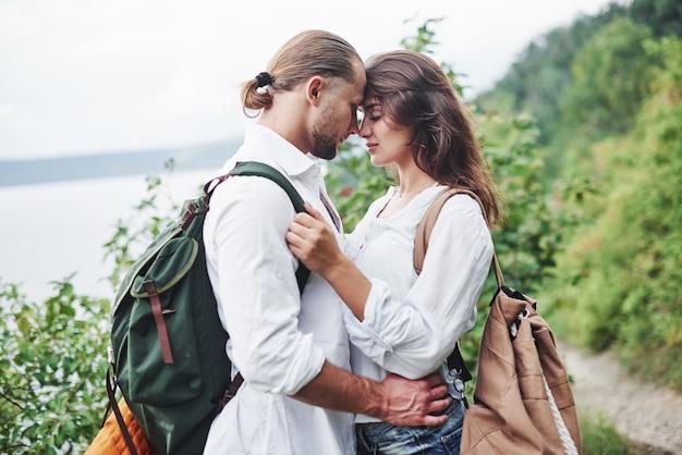 Jovem casal decidiu passar as férias de forma ativa perto do lago ao fundo.