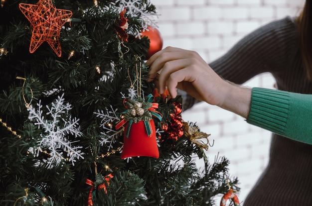 Jovem casal decorando na linda árvore de natal em casa