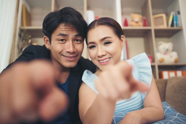 Jovem casal dedo aponta para a câmera
