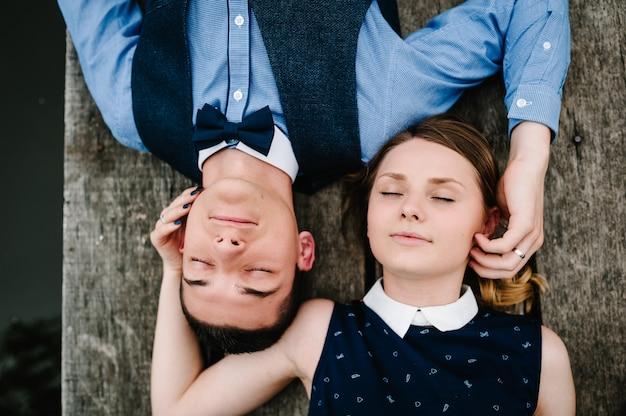 Jovem casal deitado em uma ponte de madeira