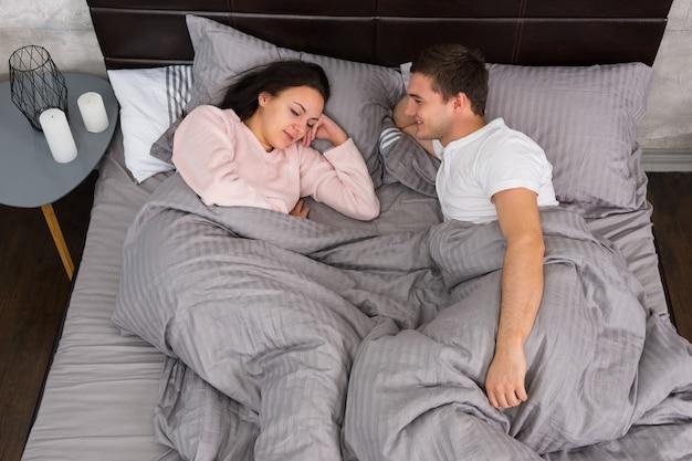 Jovem casal deitado na cama e de pijama perto da mesa de cabeceira com velas no quarto em estilo loft em tons de cinza