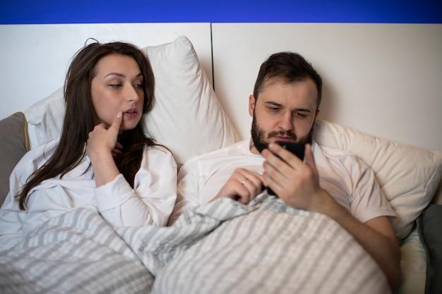 Jovem casal deitado na cama, homem usando telefone celular, ignorando sua esposa