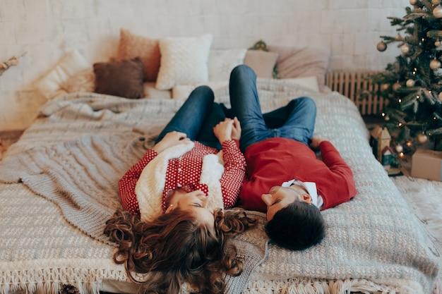 Jovem casal deitado na cama, sorrindo com as cabeças de cabeça para baixo