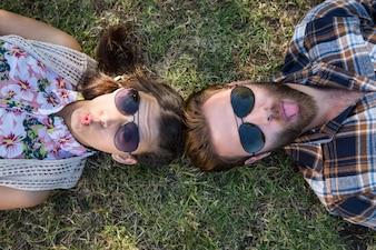 Jovem casal deitado na grama, sorrindo na câmera