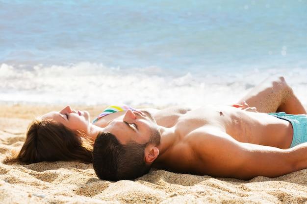 Jovem casal deitado na praia de areia na costa do mar