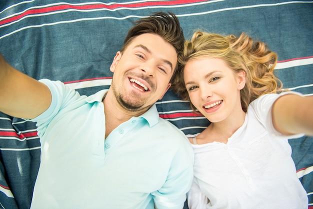 Jovem casal deitado no gramado do parque e fazendo selfie.