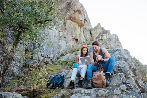 Jovem casal descansando e usando um computador tablet enquanto está sentado em uma montanha rochosa