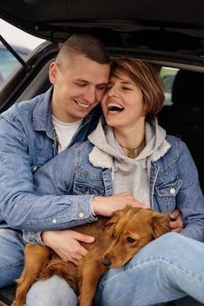 Jovem casal descansando no carro com seu cachorro.