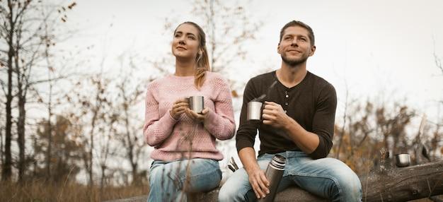 Jovem casal descansar bebendo café quente na natureza