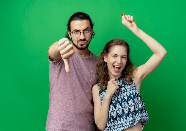 Jovem casal descontente, homem mostrando os polegares para baixo, ao lado de sua namorada feliz sobre fundo verde