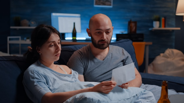 Jovem casal desesperado lendo aviso de despejo em papelada
