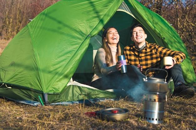 Jovem casal desfrutando ao ar livre, acampar na natureza com tenda bebe chá por uma fogueira