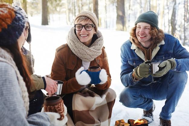 Jovem casal desfrutando de bebidas na floresta de inverno