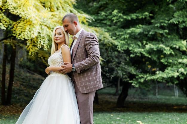 Jovem casal desfrutando de momentos românticos enquanto caminhava no parque. elegante noiva e noivo posando e beijando no parque no dia do casamento. noiva elegante em lindo vestido branco, noivo de terno.