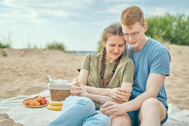Jovem casal desfrutando de piquenique na praia, abraçando e segurando copos