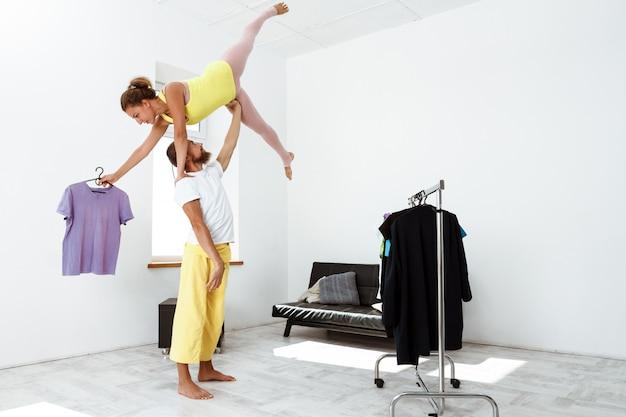 Jovem casal desportivo bonito parceiro de treino yoga asanas em casa.