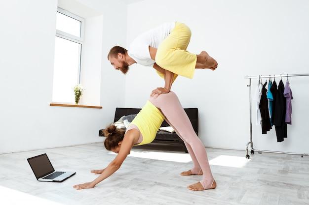 Jovem casal desportivo bonito parceiro de treino yoga asanas em casa