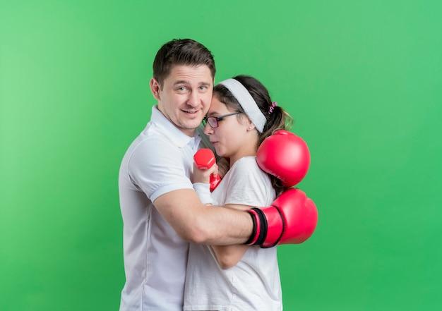 Jovem casal desportivo com luvas de boxe abraçando a namorada feliz e positivo em pé sobre a parede verde
