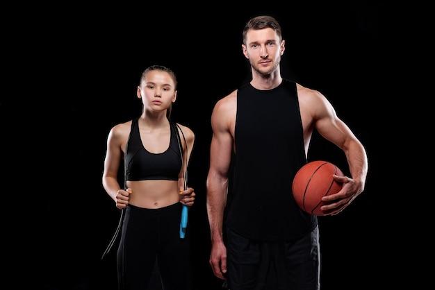 Jovem casal desportivo com roupa desportiva preta segurando corda de pular e bola enquanto treina na academia ou centro esportivo