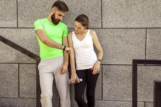 Jovem casal desportivo está descansando e checando seu relógio de fitness juntos, bebendo água. conceitos de esporte e tecnologia.
