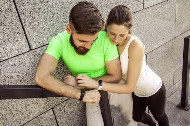 Jovem casal desportivo está descansando e checando seu relógio de fitness juntos. conceitos de esporte e tecnologia.