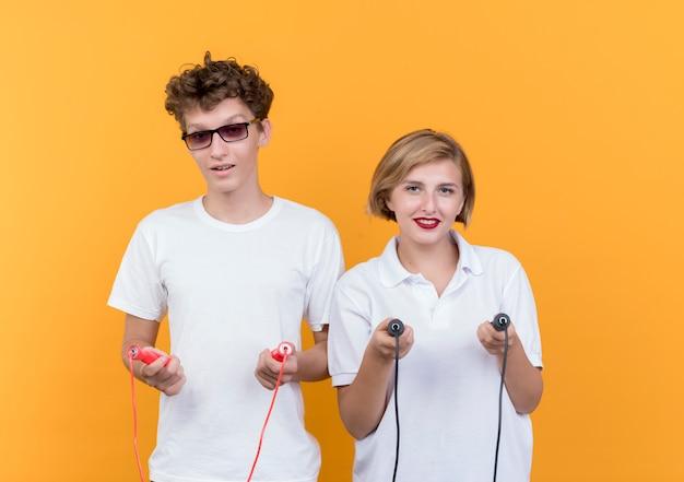 Jovem casal desportivo, homem e mulher, a pular cordas sorrindo em pé sobre a parede laranja
