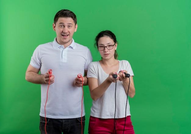 Jovem casal desportivo, homem e mulher, a pular cordas sorrindo em pé sobre a parede verde