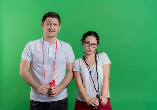 Jovem casal desportivo, homem e mulher, com a confusão de pular cordas em pé sobre a parede verde
