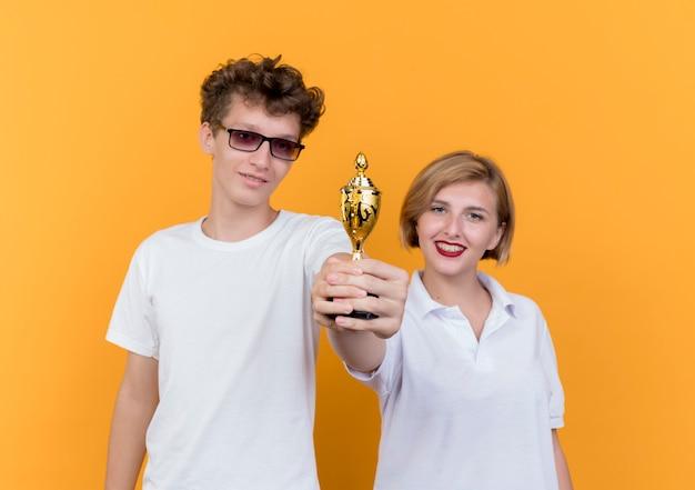 Jovem casal desportivo, homem e mulher, juntos, mostrando o troféu sorrindo com rostos felizes em pé sobre a parede laranja
