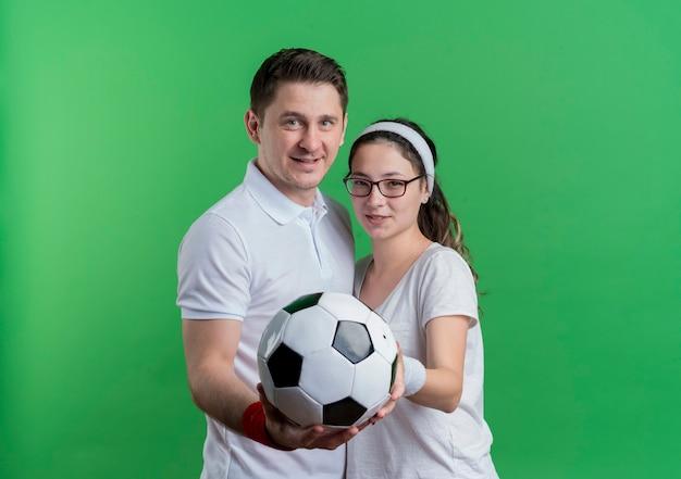 Jovem casal desportivo, homem e mulher juntos, segurando uma bola de futebol sorrindo sobre o verde