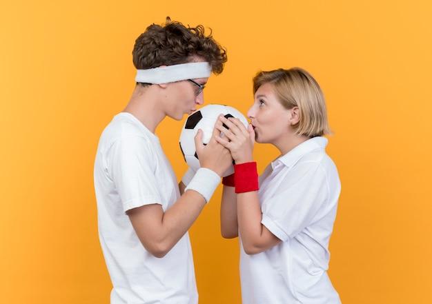 Jovem casal desportivo, homem e mulher, olhando um para o outro, segurando uma bola de futebol e beijando-a em pé sobre uma parede laranja