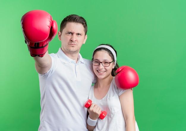 Jovem casal desportivo mulher com halteres e homem com luvas de boxe sorrindo em pé sobre a parede verde
