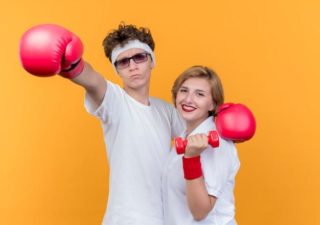 Jovem casal desportivo mulher com halteres e homem com luvas de boxe sorrindo em pé sobre uma parede laranja