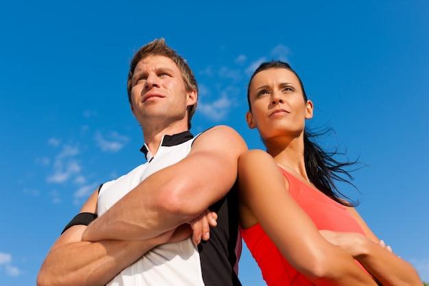 Jovem casal desportivo olhando longe da câmera