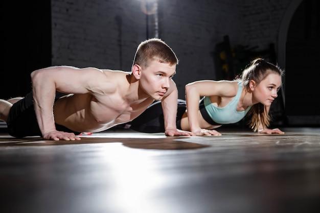 Jovem casal desportivo treinando no ginásio.