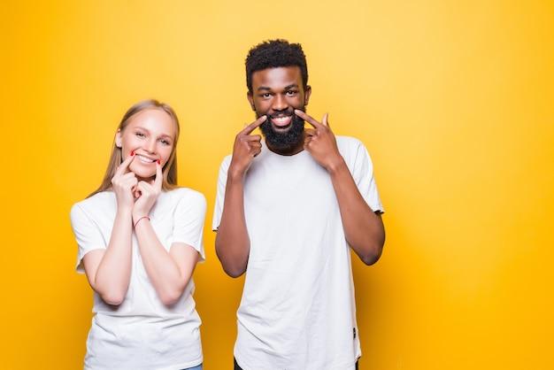 Jovem casal diversificado apontando na bochecha, isolado na parede amarela