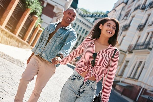 Jovem casal diversificado caminhando pelas ruas da cidade de mãos dadas, sorrindo animado