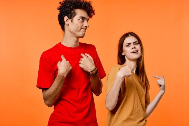 Jovem casal divertido amizade comunicação fundo laranja moda