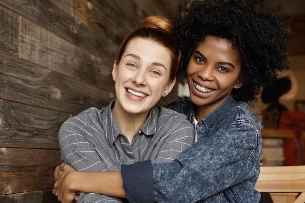 Jovem casal do mesmo sexo se abraçando ternamente em um café