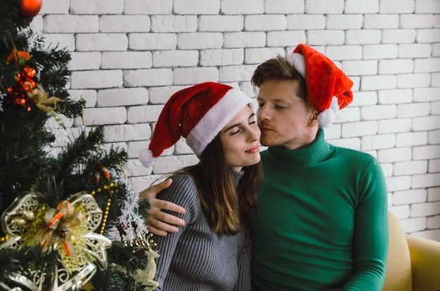 Jovem casal doce caucasiano com chapéu de papai noel vermelho desfrutar e beijar sua namorada no sofá com a árvore de natal comemorando em casa