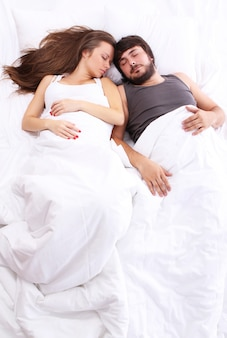 Jovem casal dorme na cama