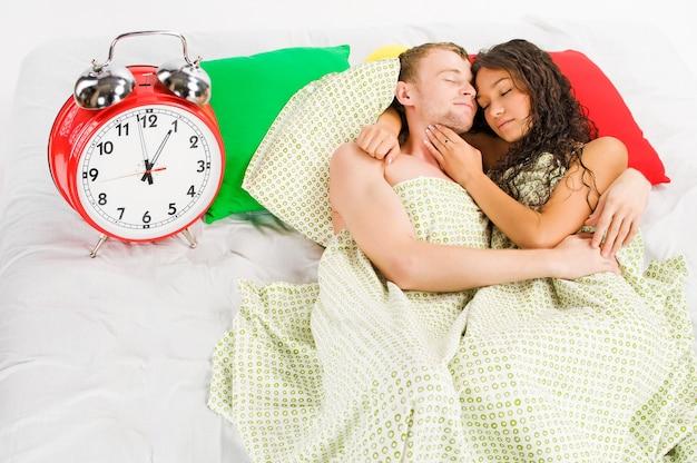 Jovem casal dormindo junto e ignorando a campainha do despertador